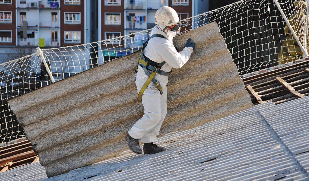 UKAS experienced asbestos surveys - Worker remove asbestos from commercial building